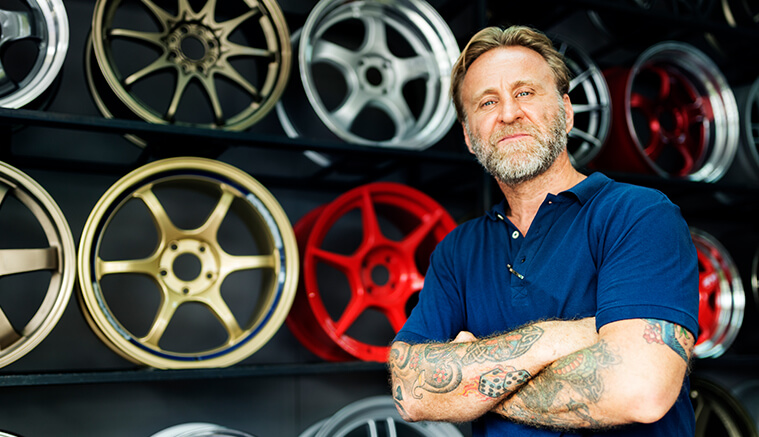 Man with tattoo sleeves standing in front of custom wheels
