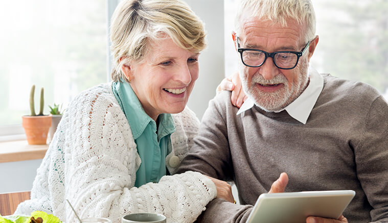 Older couple reading about health savings account on ipad