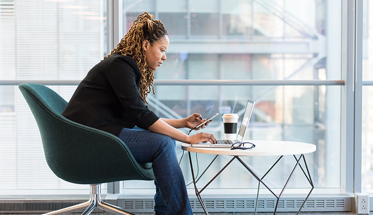 Black woman working at a coffee table with laptop and phone researching retirement plans