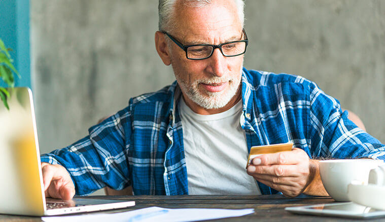 65 year old man making a purchase online with debit card