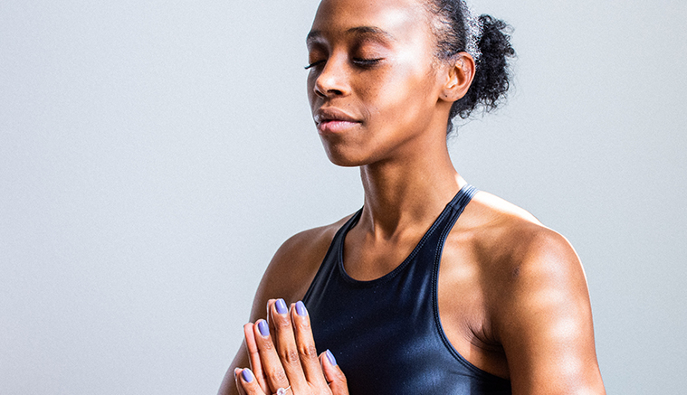 Black female in workout attire meditating to promote the importance of wellness discount program