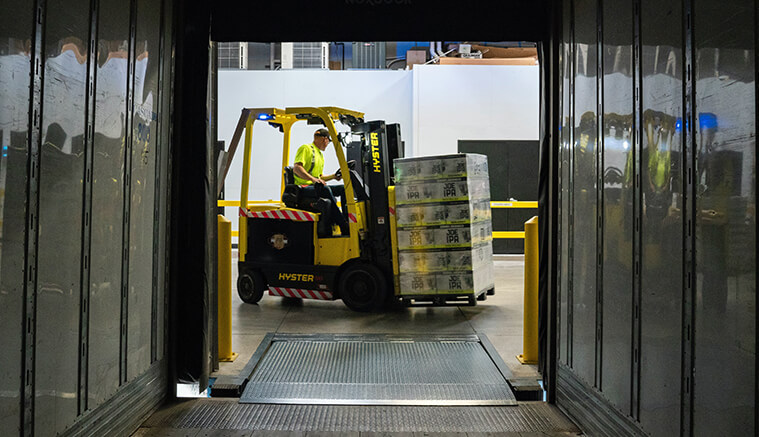 Man driving a forklift in a warehouse moving boxes