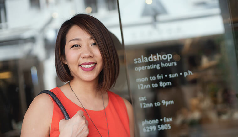 Asian woman standing outside of her salad shop