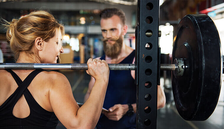Male personal trainer assisting female client perform squats on a smith machine to highlight the importance of accident insurance