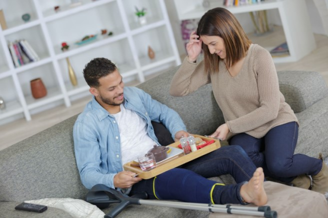 Female bringing food try to man of color with an injured leg sitting on sofa with crutches to promote disability insurance