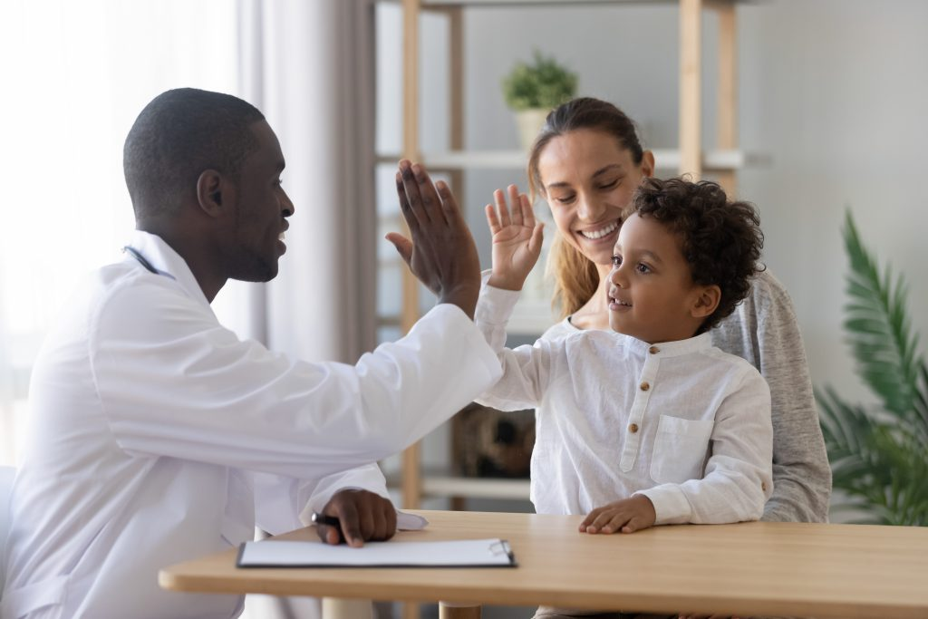 Black Pediatrician give high five to mixed race child sitting on mother's lap