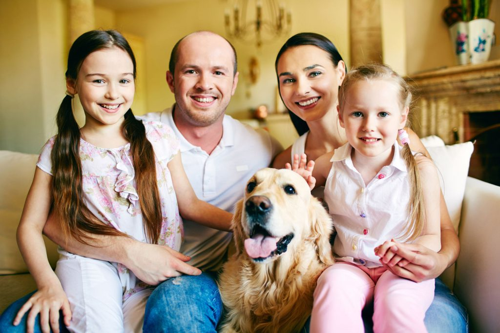 Family smiling at camera with dog