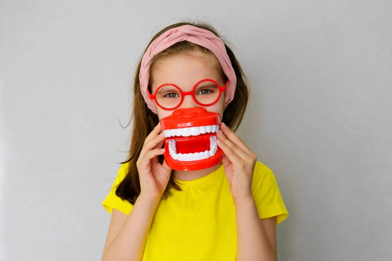 child wearing glasses and tooth model