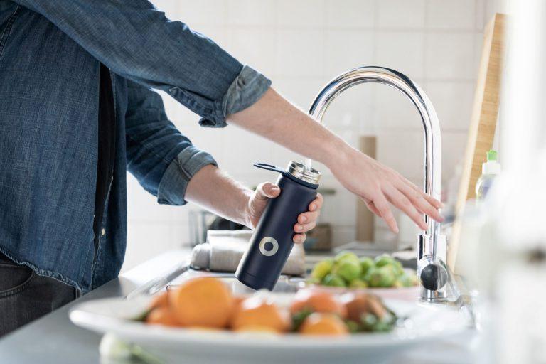 refilling water bottle in kitchen healthy food
