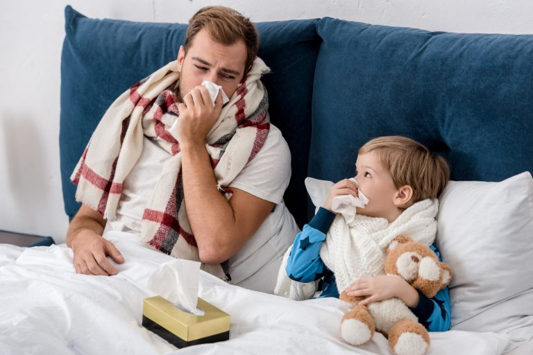 Self employed father in bed sick with his sick son