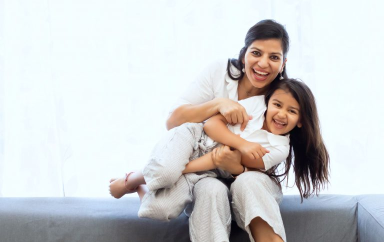 Indian mother and daughter snuggling on sofa