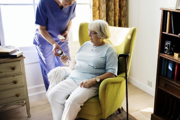 home nurse giving water to retired 65 year old lady